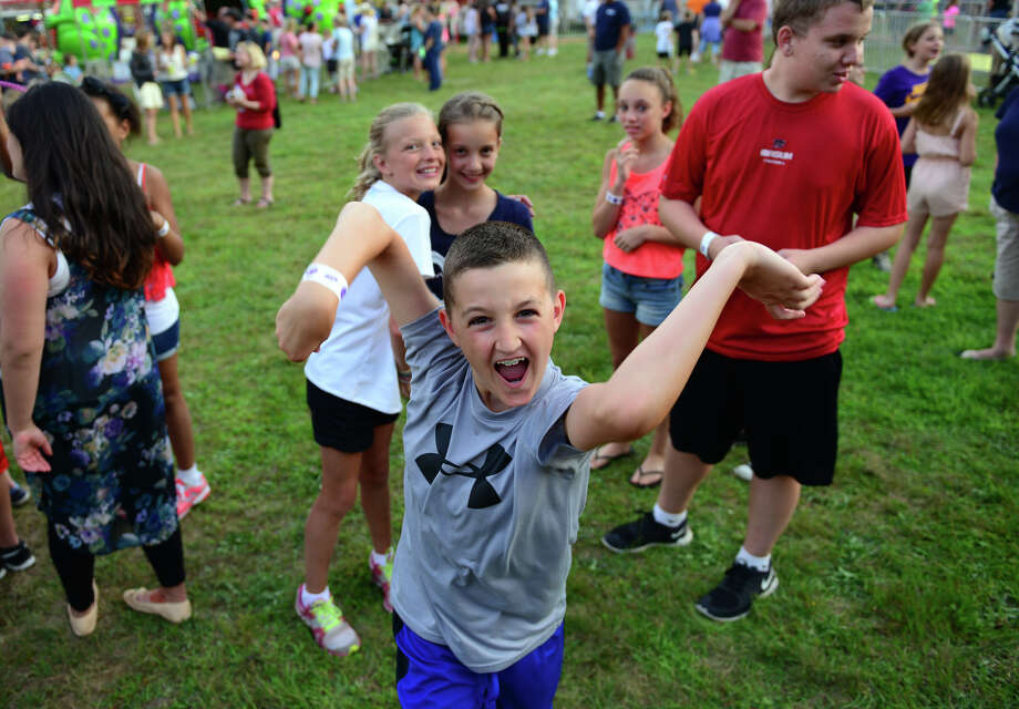 Luke Sawyer, 10, of Monroe, shows off his dance moves as he enjoys the Monroe Fire Deparment Carnival at Fireman's Field in Monroe, Conn. on Thursday July 10, 2014. The carnival, located at the intersections of Route 110 and 111, continues through Saturday July 12th. Photo: Christian Abraham / Connecticut Post