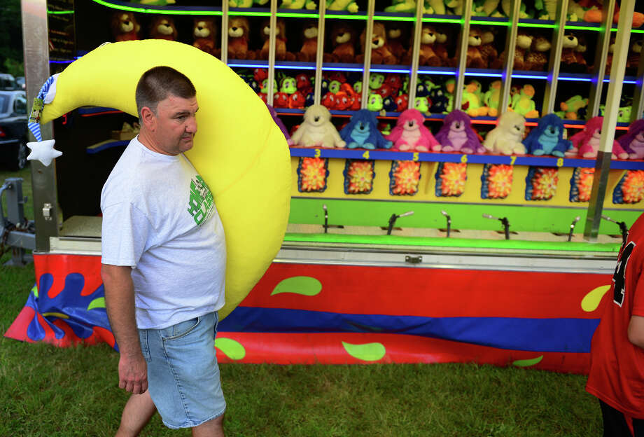 Jerry Nyarady, of Trumbull, carries the stuffed banana his son J.T. won during the Monroe Fire Deparment Carnival at Fireman's Field in Monroe, Conn. on Thursday July 10, 2014. The carnival, located at the intersections of Route 110 and 111, continues through Saturday July 12th. Photo: Christian Abraham / Connecticut Post