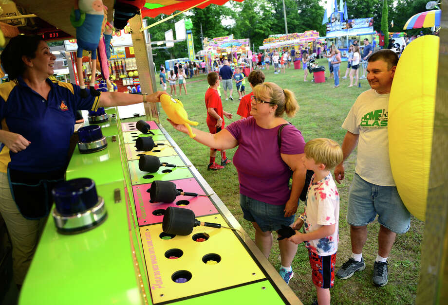 Cheryl Nyarady, of Trumbull, grabs the prize her son Cody, 8, won during the Monroe Fire Deparment Carnival at Fireman's Field in Monroe, Conn. on Thursday July 10, 2014. The carnival, located at the intersections of Route 110 and 111, continues through Saturday July 12th. Photo: Christian Abraham / Connecticut Post
