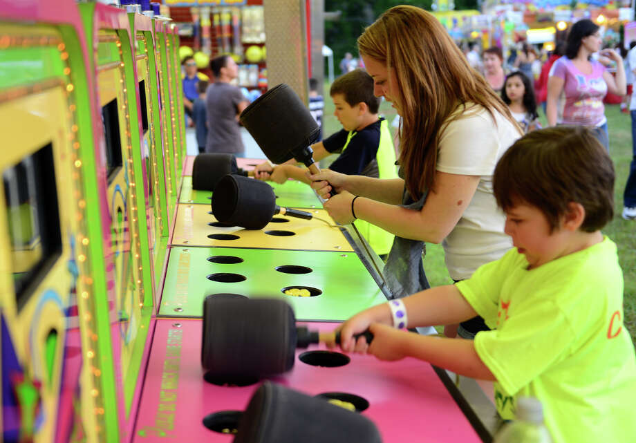 Jack Steferak, 8, in back, Hannah Schwartz, in center, and her brother Jonah, 9, play Whack-A-Mole, during the Monroe Fire Deparment Carnival at Fireman's Field in Monroe, Conn. on Thursday July 10, 2014. The carnival, located at the intersections of Route 110 and 111, continues through Saturday July 12th. Photo: Christian Abraham / Connecticut Post