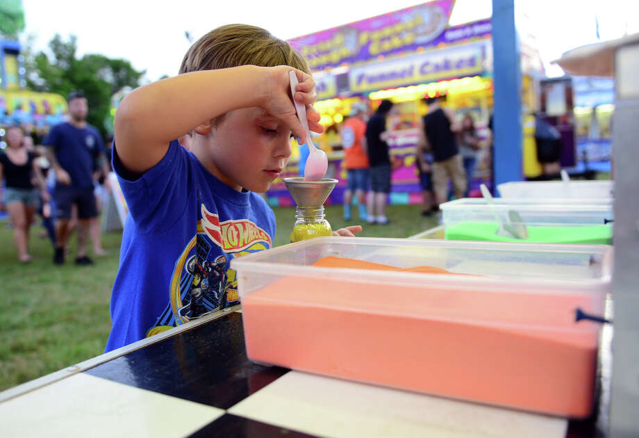 Danny Moran, 4, of Long Beach , NY, fills his bottle with sand, during the Monroe Fire Deparment Carnival at Fireman's Field in Monroe, Conn. on Thursday July 10, 2014. The carnival, located at the intersections of Route 110 and 111, continues through Saturday July 12th. Photo: Christian Abraham / Connecticut Post