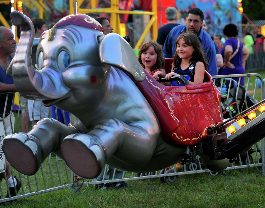 Calista Mitrakis, 5, of Monroe, and her sister Alexis, 7, at right, ride Dumbo at the Monroe Fire Deparment Carnival at Fireman's Field in Monroe, Conn. on Thursday July 10, 2014. The carnival, located at the intersections of Route 110 and 111, continues through Saturday July 12th. Photo: Christian Abraham / Connecticut Post