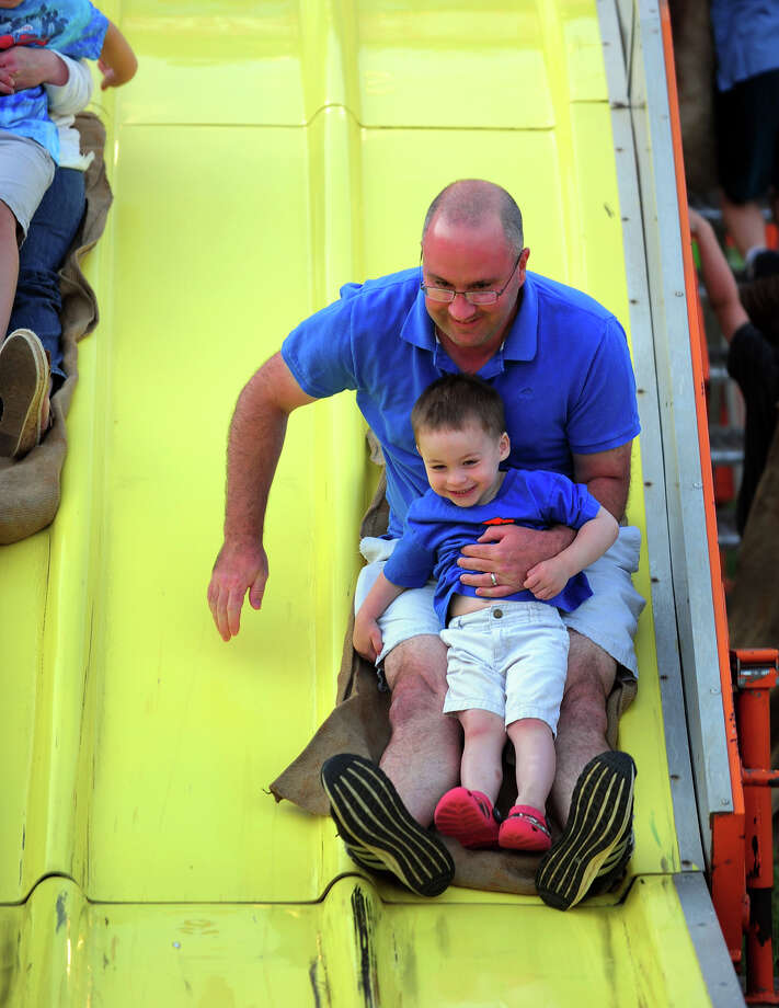 Adam Lee, of Easton, and his son Cody, 2, come down the slide ride durnig the Monroe Fire Deparment Carnival at Fireman's Field in Monroe, Conn. on Thursday July 10, 2014. The carnival, located at the intersections of Route 110 and 111, continues through Saturday July 12th. Photo: Christian Abraham / Connecticut Post
