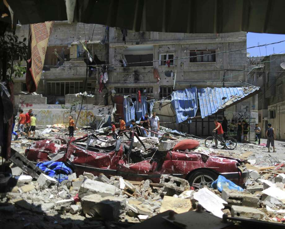 People gather in a street to inspect damage after an airstrike in Gaza City. As Israel's air campaign entered its third day, the Palestinian death toll rose to 78, say Gaza officials. Photo: Wissam Nassar / New York Times / NYTNS