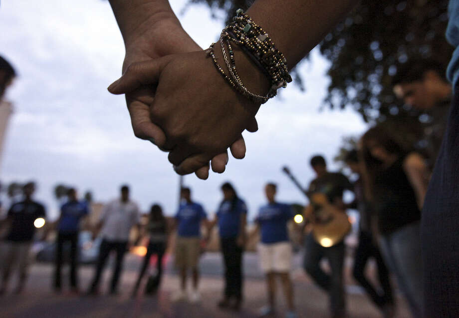 Members of Minority Affairs Council take part in a vigil for migrants held outside Sacred Heart Church in McAllen. Photo: Edward A. Ornelas / San Antonio Express-News / © 2014 San Antonio Express-News