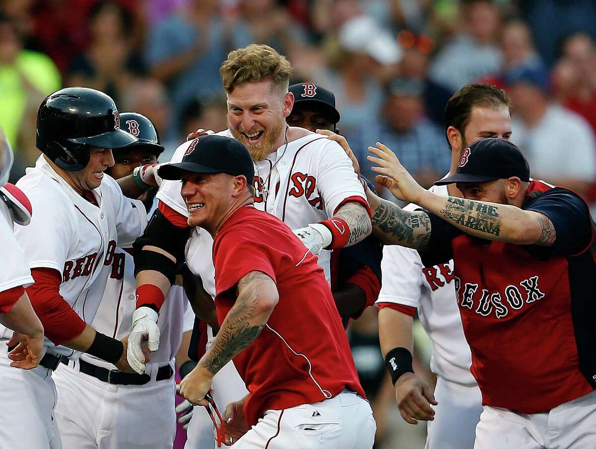 BOSTON, MA - JULY 10: Mike Carp #37 of the Boston Red Sox celebrates with teammates after knocking in the winning run in the tenth inning against the Chicago White Sox iat Fenway Park on July 10, 2014 in Boston, Massachusetts. (Photo by Jim Rogash/Getty Images) ORG XMIT: 477586237