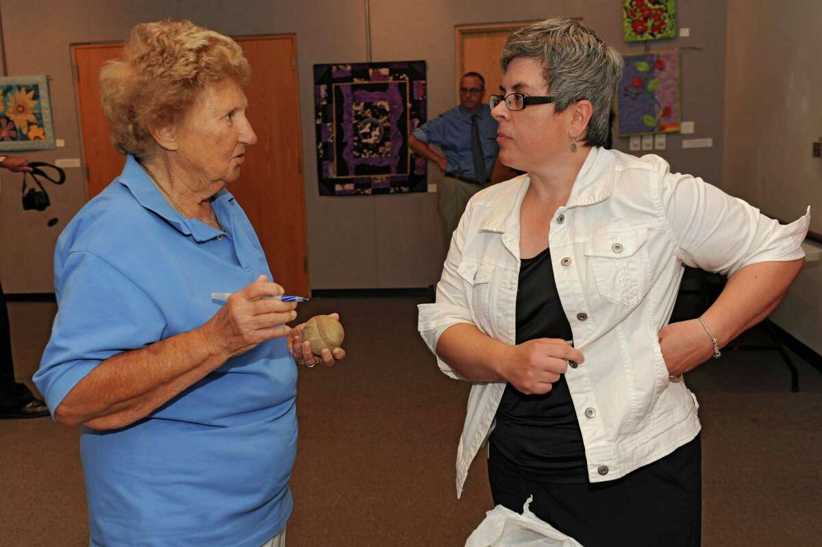 Dolly Konwinski, who was an AAGPBL player during the 1947 - 1952 seasons signs a baseball for Debra Foley of Albany, right, at the Guilderland Library on Thursday, July 10, 2014 in Guilderland, N.Y. Debra was getting a ball signed for her friend Susan. A popular movie