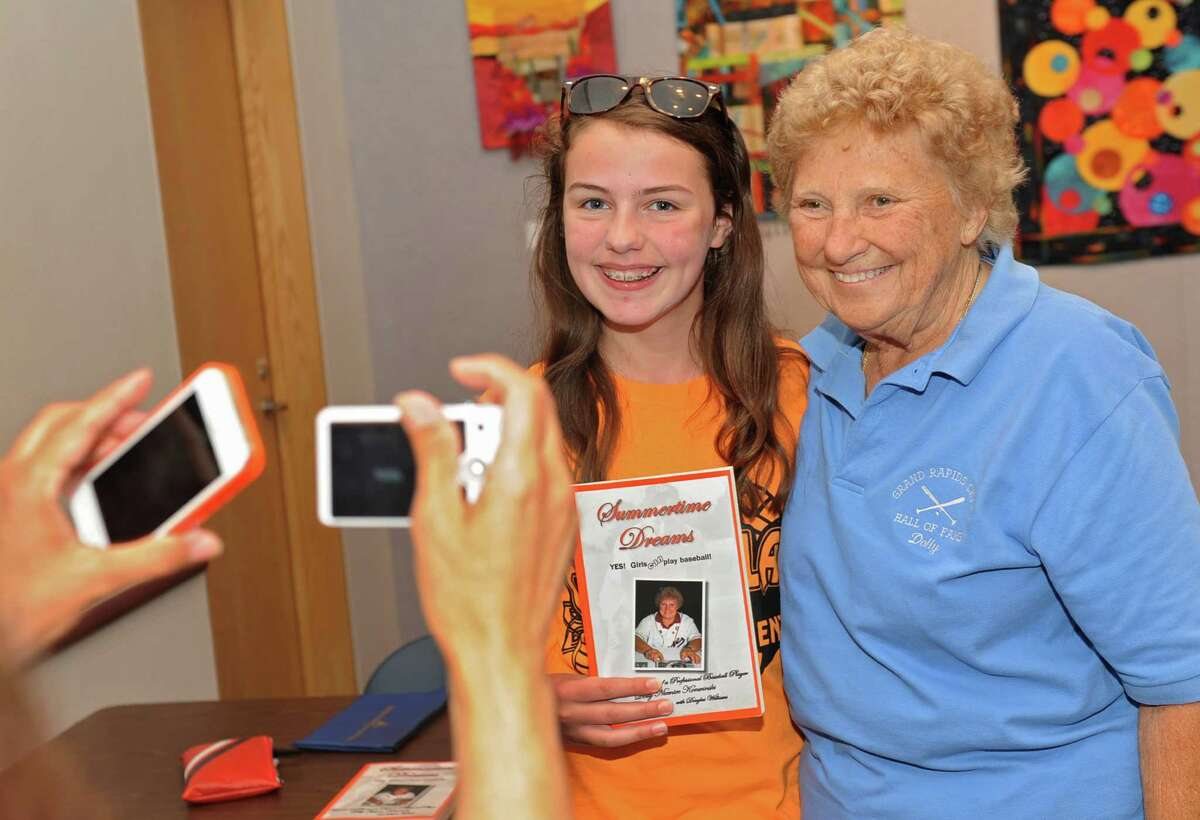 Jillian Creighton of Guilderland, 12, gets her photo taken by her mom Marie with Dolly Konwinski, who was an AAGPBL player during the 1947 - 1952 seasons, at the Guilderland Library on Thursday, July 10, 2014, in Guilderland, N.Y. A popular movie