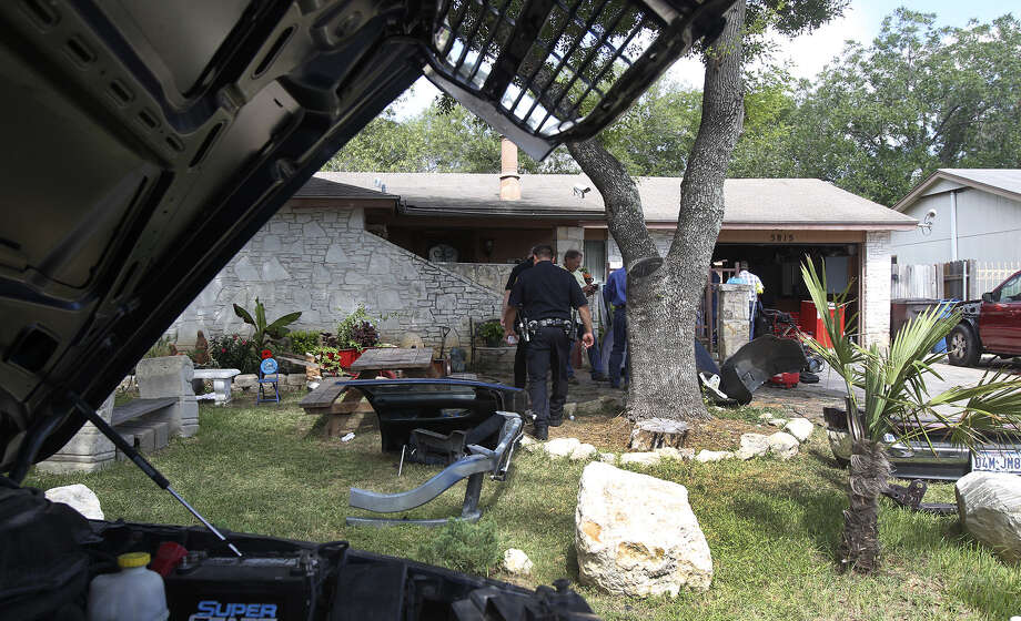 San Antonio police say a 911 call was made from this West Side home for burglars in action, but police noticed an abundance of car parts at the home — laying out chassis, doors of pickup trucks, bumpers, hoods and other car parts — and found no evidence of burglary. A man, not yet identified, faces charges of theft and possessing stolen property. Photo: Photos By John Davenport / San Antonio Express-News / ©San Antonio Express-News/John Davenport