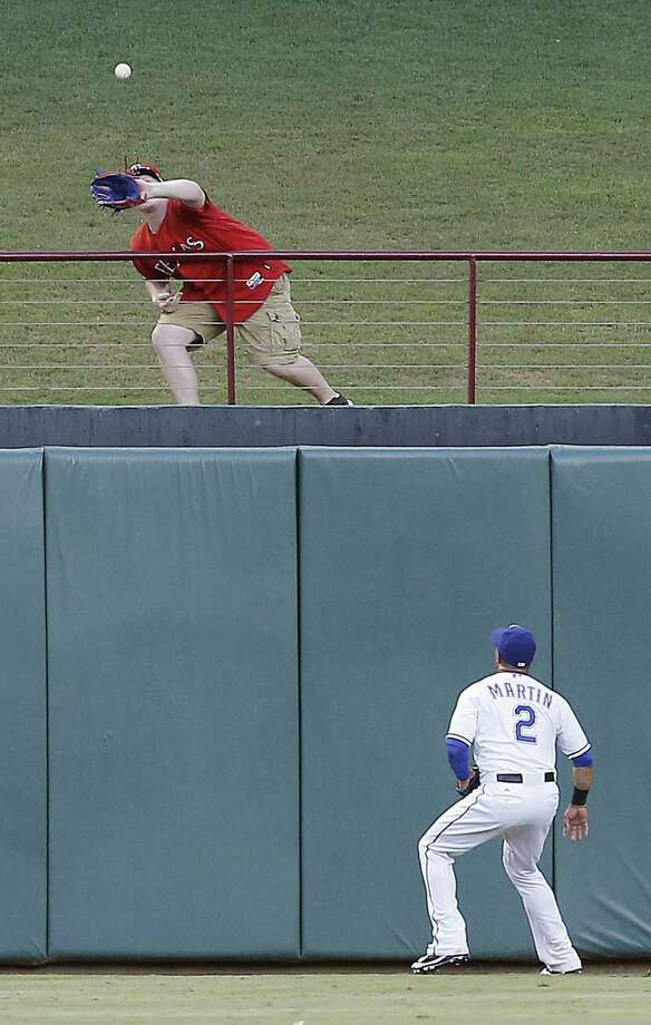 Rangers center fielder Leonys Martin watches a fan catch a Mike Trout three-run homer that's out of his reach. The Angels' slugger had four hits to help fuel Los Angeles' blowout win. Photo: Brandon Wade / Fort Worth Star-Telegram / Fort Worth Star-Telegram