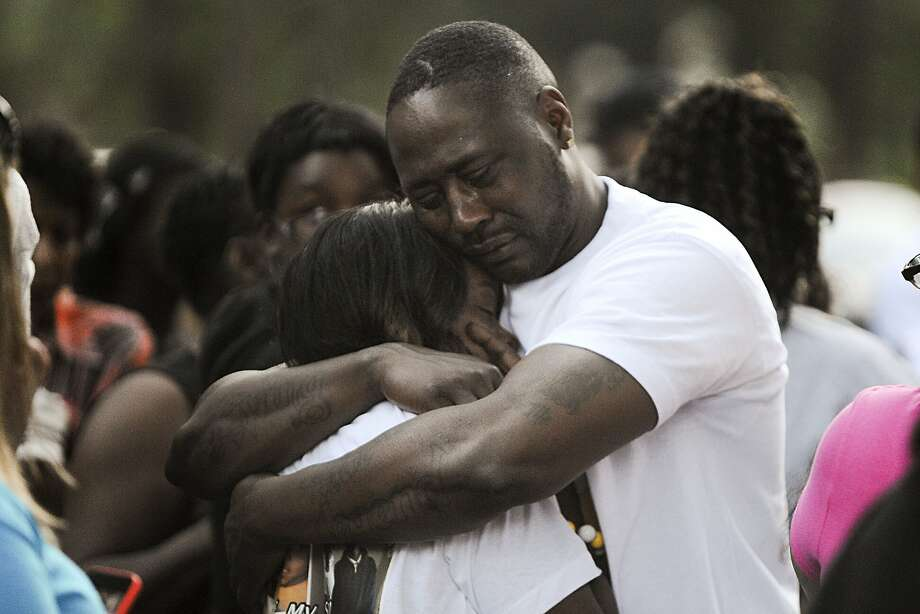 Robert Fletcher, stepfather, and Marquita Render, mother of Dmetrius Washington, a 14-year-old Muskegon Heights, Mich., shooting victim, embrace during an anti-violence candlelight vigil Thursday, July 10, 2014, at the area where he was shot. Dmetrius Washington died of a gunshot wound early Wednesday. (AP Photo/The Muskegon Chronicle, Madelyn Hastings) Photo: Madelyn Hastings, Associated Press