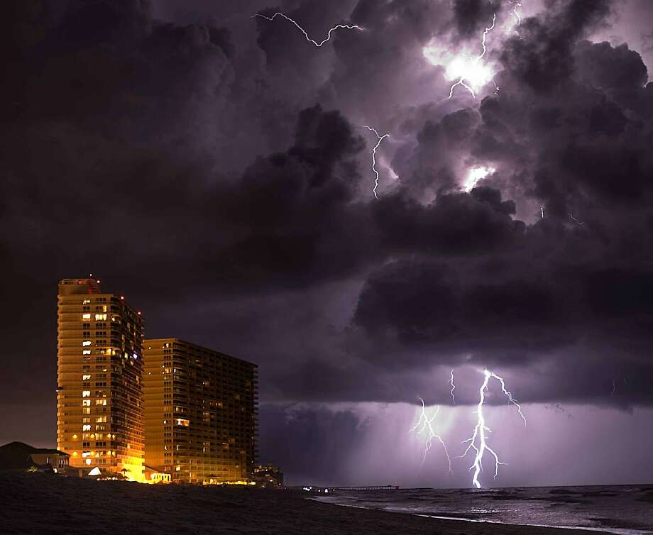Lighting from an approaching thunder storm strikes near the shore in Panama City Beach, Fla., on Thursday, July 10, 2014. (AP Photo/The Decatur Daily,Brennen Smith) MBO Photo: Brennen Smith, Associated Press