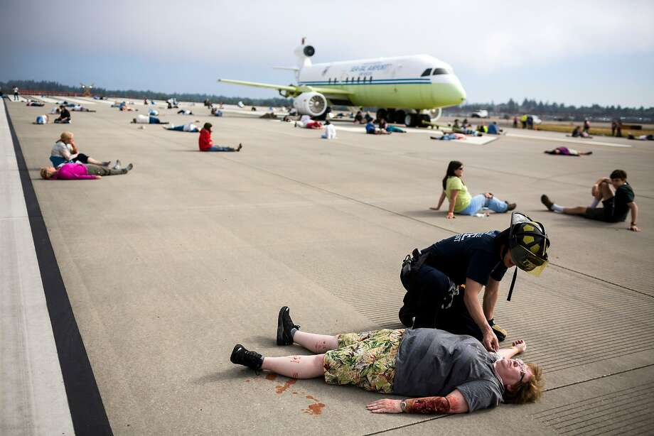 Port of Seattle and regional responders care to nearly 300 victim volunteers at a mock full-scale emergency exercise simulating an aircraft accident Thursday, July 10, 2014, at Sea-Tac International Airport in SeaTac, Wash. The Port of Seattle is organizing region-wide emergency response partners and incorporating lessons learned from last year's aircraft incident in San Francisco. (AP Photo/seattlepi.com, Jordan Stead) Photo: Jordan Stead, Associated Press