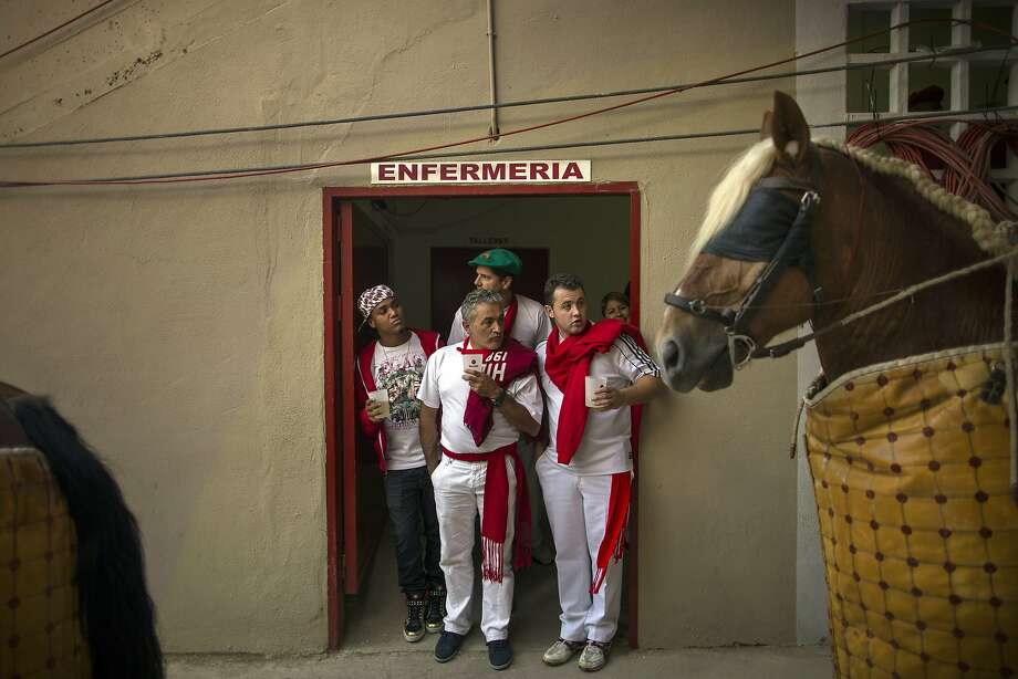 "Revelers look at Spanish ""Picadors"" horses  waiting to go on the bullfighting arena during a bullfight of the San Fermin festival in Pamplona, Spain, Thursday, July 10, 2014. Revelers from around the world arrive to Pamplona every year to take part in some of the eight days of the running of the bulls. Banner reads ""nursing"". (AP Photo/Andres Kudacki) Photo: Andres Kudacki, Associated Press"