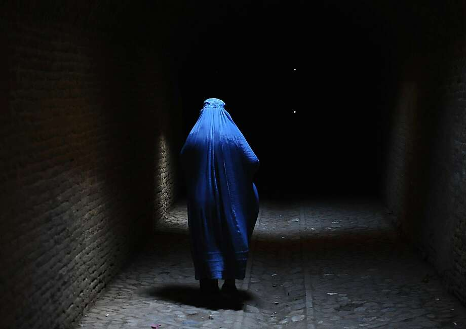 TOPSHOTS A burqa-clad Afghan woman walks in the old part of Herat on July 10, 2014. Afghanistan remains at war, with civilians among the hardest hit as the Taliban wage an increasingly bloody insurgency against the government. AFP PHOTO/AREF KARIMIAref Karimi/AFP/Getty Images Photo: Aref Karimi, AFP/Getty Images