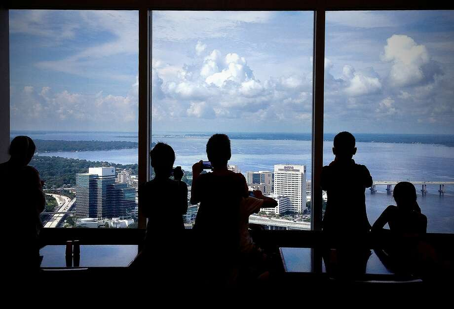 Photographers from the Museum of Contemporary Art Jacksonville photography camp take pictures from the 42nd floor of the Bank of America tower on Thursday, July 10, 2014, in Jacksonville, Fla. The young photographers are spending about half their time shooting pictures and the other half on the computer learning Photoshop techniques. Mario Peralta, their instructor, says the campers have been working on a variety of assignments including; collages, silhouettes, textures and multiple exposures.  (AP Photo/Florida Times-Union, Bruce Lipsky) Photo: Bruce Lipsky, Associated Press