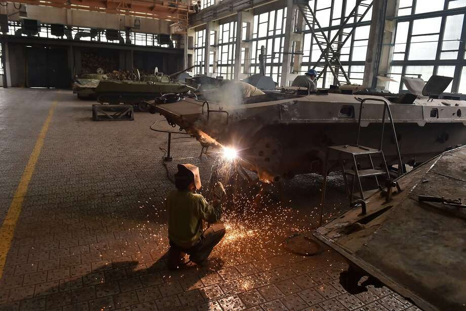 TOPSHOTS  A worker welds the body of an armoured personnel carrier (APC) during repair work in a tank plant in Zhytomyr, some 150 km west of Kiev, on July 10, 2014. The workers and employees of the plant repair armored vehicles and tanks which were used by Ukrainian governmen forces during the assault on pro-Russian insurgents in the east of the country. Ukraine warned on July 9 that its assault on pro-Russian insurgents may last another month and rejected calls for a ceasefire as it moved tanks within striking distance of the rebels' two remaining strongholds.  AFP PHOTO/ SERGEI SUPINSKYSERGEI SUPINSKY/AFP/Getty Images Photo: Sergei Supinsky, AFP/Getty Images