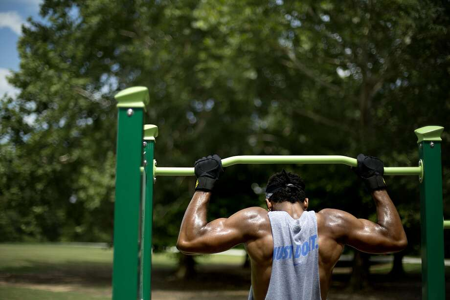 Antonio Williams, of Atlanta, works out on a pull-up bar in Piedmont Park, Thursday, July 10, 2014, in Atlanta. (AP Photo/David Goldman) Photo: David Goldman, Associated Press