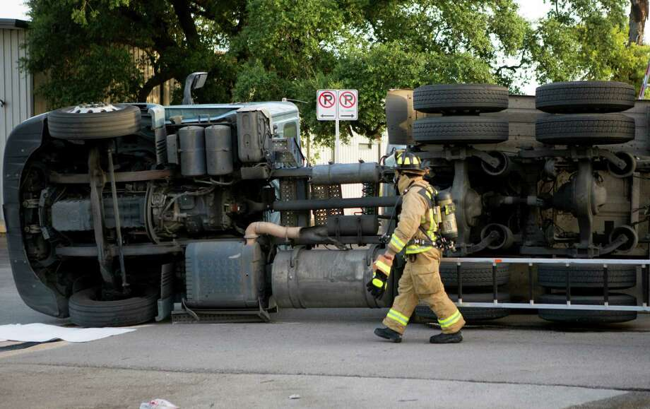 Firefighters work the scene of an overturned big rig wreck in the 1200 block of Parker near Nett, Friday, July 11, 2014, in Houston. Hazmat units were dispatched to the wreck to help crews clear the scene. Photo: Cody Duty, Houston Chronicle / © 2014 Houston Chronicle