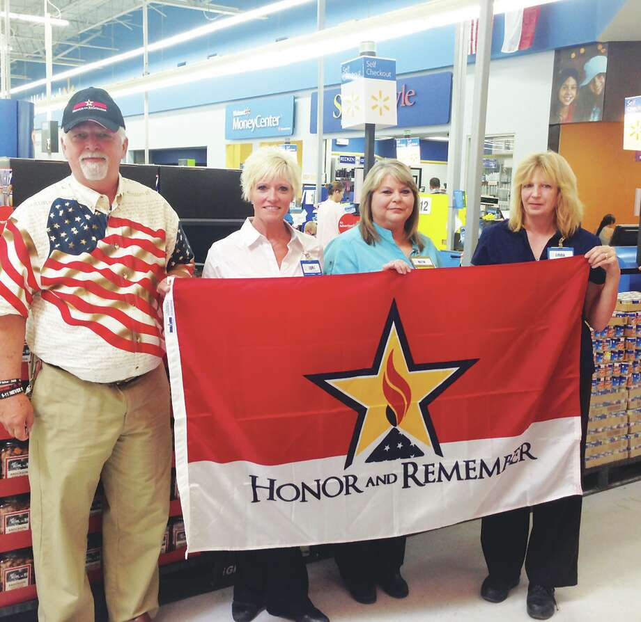 Roy James presents an Honor and Remember flag to the Jasper Wal Mart photo by Shannon Stott