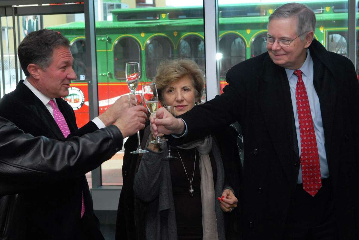 After a long dispute, Carl Kuehner, Building and Land Technology's CEO (left) and Sandy Goldstein, president of the Downtown Special Services District, celebrated the opening of the trolley connecting the downtown and South End in February. Stamford Mayor David Martin is pictured at right.