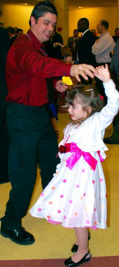 """SPECTRUM/Jason Hanakahi and his daughter, Halia, 6, show off their fancy footwork to the music of """"Cotton-Eyed Joe"""" at the Feb. 5, 2010, Sweetheart Semi-formal dance hosted by New Milford Girl Scout Troop Nos. 40300 and 40302 at New Milford High School.  Photo by Deborah Rose Photo: Deborah Rose / The News-Times"""
