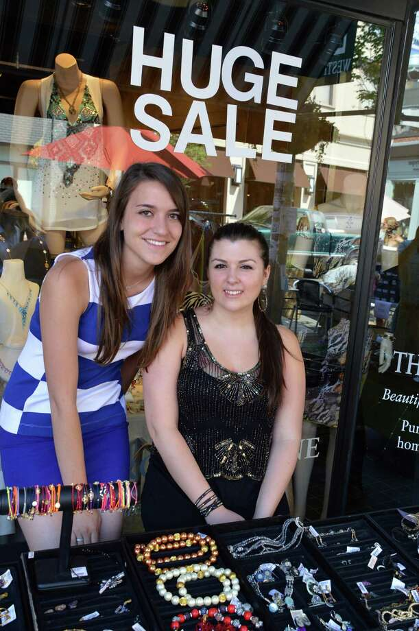 Camila Reinhardt, left, and Niki Puglisi, of The Brownstone said they wished that Westport's sidewalk sale was not held the same day as sales in surrounding towns so that more customers might come to the local event. Photo: Jarret Liotta / Westport News