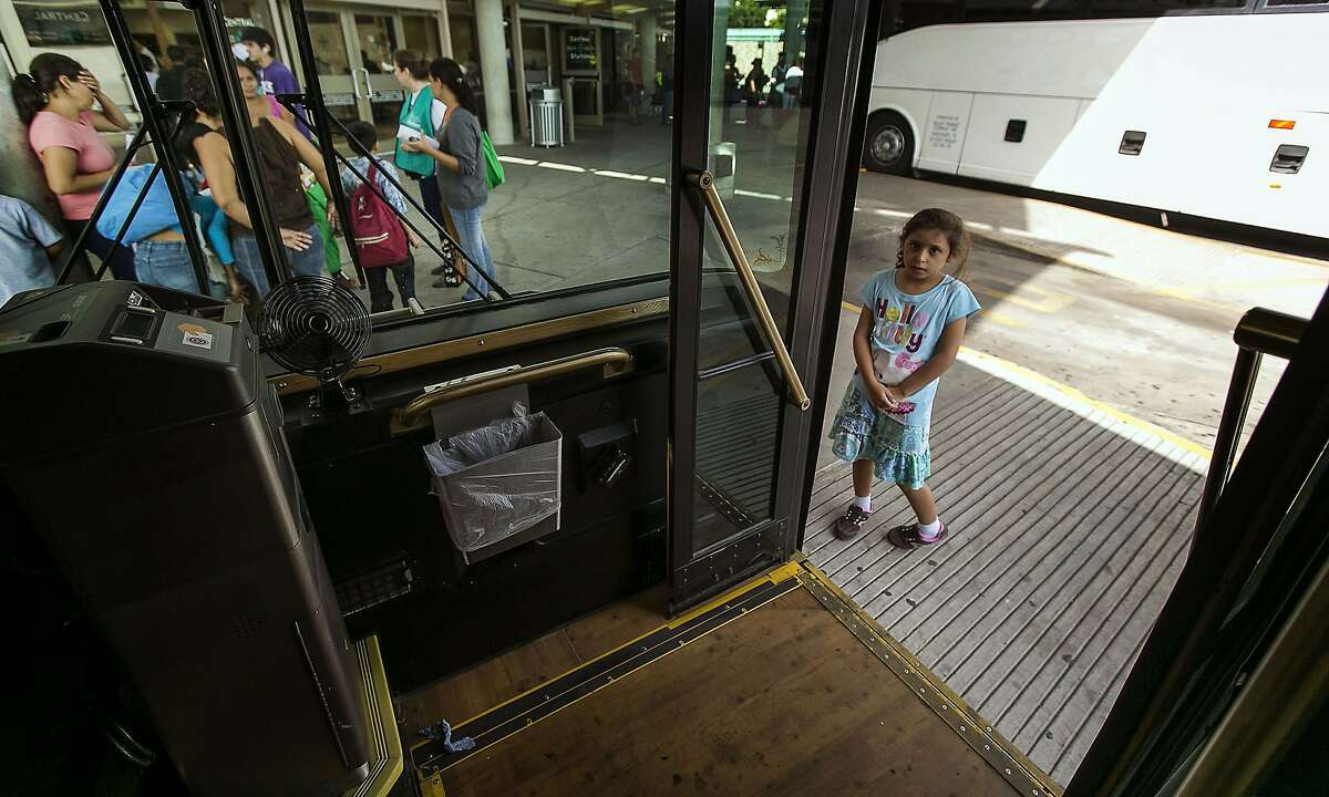 In this photo taken July 4, 2014, eight-year-old Gabby, of El Salvador, peaks into a city shuttle bus as she waits for her mother and sister after they and other immigrants and their children were released by U.S. Customs and Border Protection Services at the city bus station in McAllen, Texas. About 90 Hondurans a day cross illegally from Mexico into the U.S. at the Rio Grande near McAllen, according to the Honduran Consulate, and the families are then brought to Central Station in McAllen and each is released on their own recognizance. Though most travelers have enough money to purchase their own bus tickets to meet family in cities across the U.S., many have nowhere to stay before the buses leave, and most are in need of rest, medical attention and sustenance. It falls to the local government and charities to welcome the uninvited visitors to America. Tens of thousands have also fled to the U.S. from El Salvador and Guatemala to escape violence. (AP Photo/Austin American-Statesman, Rodolfo Gonzalez)