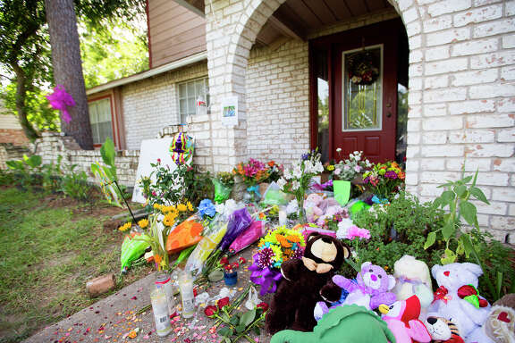 A memorial is seen in front of the home where seven people were shot, Friday, July 11, 2014, in Spring. The shooting took place Wednesday killing six people including four children and two adults, who were shot to death after an apparent domestic dispute.