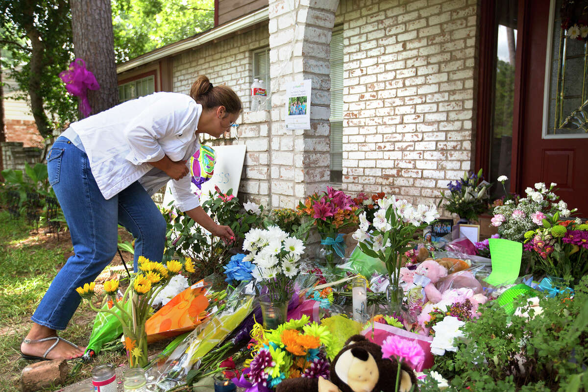 Toni Parker places a flower at the site of a memorial in front of the home where seven people were shot, Friday, July 11, 2014, in Spring. The shooting took place Wednesday killing six people including four children and two adults, who were shot to death after an apparent domestic dispute.