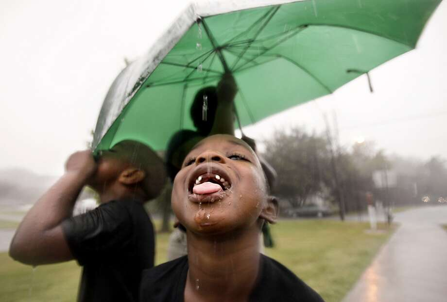 Umbrella runoff is the tastiest water of all: Jimmy and Jimon Ruffin quench their thirst while waiting for the bus with their mother in Raleigh, N.C. Photo: Corey Lowenstein, Associated Press