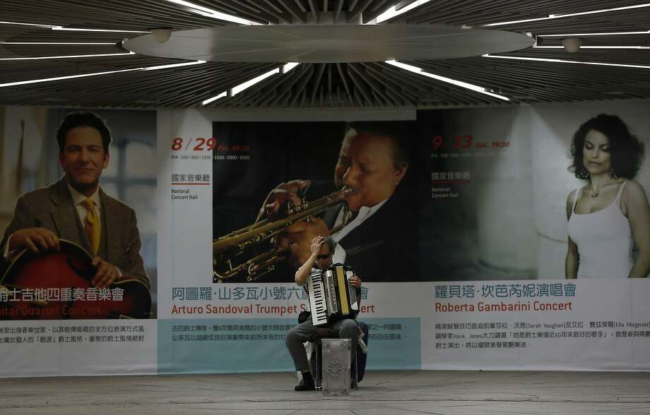 The one-man orchestra under the concert hall: A blind accordionist plays in the walkway below the National Concert Hall in Taipei. Photo: Wally Santana, Associated Press