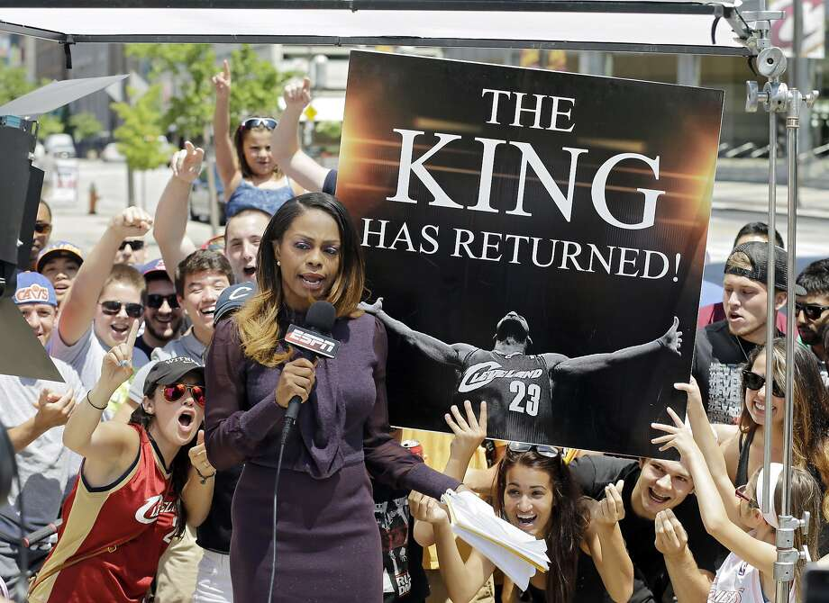 Boy, they got that sign made fast: Fans whoop it up behind an ESPN reporter outside the Quicken Loans Arena in Cleveland after LeBron James announced he would return to the Cavaliers. Photo: Mark Duncan, Associated Press