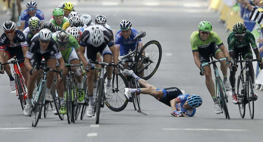 American Andrew Talansky tumblesas the pack sprints for the finish line in the seventh stage of the Tour de France in Nancy. Talansky  hurt his shoulder and had to walk his damaged bike across the finish. Photo: Peter Dejong, Associated Press