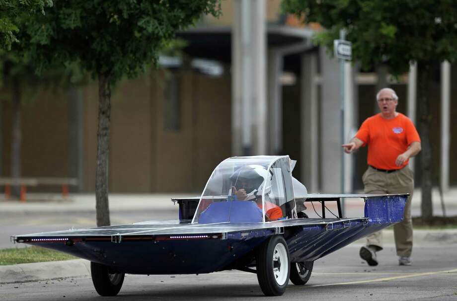 Joe Dungan, right, follows Ricardo Sanchez, 17, as he test drives the solar car Helios 2 on Friday, July 11, 2014, at James Madison High School in San Antonio. Dungan, a chemistry teacher at the school, is the director of the Madison Solar Car Initiative, a team of students who built Helios 2 and will take it to compete in this year's Solar Car Challenge in Fort Worth. Photo: Timothy Tai, San Antonio Express-News / © 2014 San Antonio Express-News