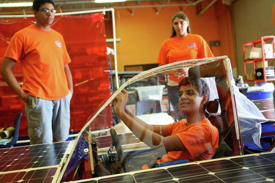 Ricardo Sanchez, 17, front, adjusts a mirror on the solar car Helios 2 as Jean-Luc Yohi, 16, back left, and Skylar Stohner, 17, watch before a test drive on Friday, July 11, 2014, at James Madison High School in San Antonio. Helios 2, built by the Madison Solar Car Initiative, a team of students at James Madison High School, will compete in this year's Solar Car Challenge, which begins July 18 in Fort Worth. Photo: Timothy Tai, San Antonio Express-News / © 2014 San Antonio Express-News