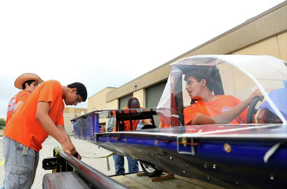 Ricardo Sanchez, right, watches as Jean-Luc Yohi, 16, adjusts a ratchet strap to tie down the solar car Helios 2 for transport on Friday, July 11, 2014, at James Madison High School in San Antonio. Helios 2, built by the Madison Solar Car Initiative, a team of students at James Madison High School, will compete in this year's Solar Car Challenge, which begins July 18 in Fort Worth. Photo: Timothy Tai, San Antonio Express-News / © 2014 San Antonio Express-News