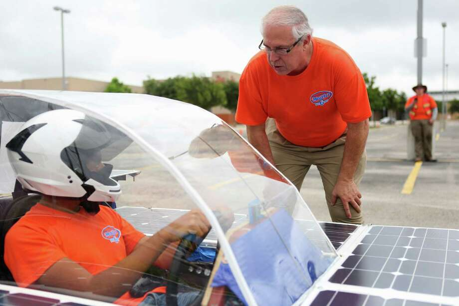 Ricardo Sanchez, 17, left, listens to Joe Dungan's instructions between test runs of the solar car Helios 2 on Friday, July 11, 2014, at James Madison High School in San Antonio. Dungan, a chemistry teacher at the school, is the director of the Madison Solar Car Initiative, a team of students who built Helios 2 and will take it to compete in this year's Solar Car Challenge in Fort Worth. Photo: Timothy Tai, San Antonio Express-News / © 2014 San Antonio Express-News