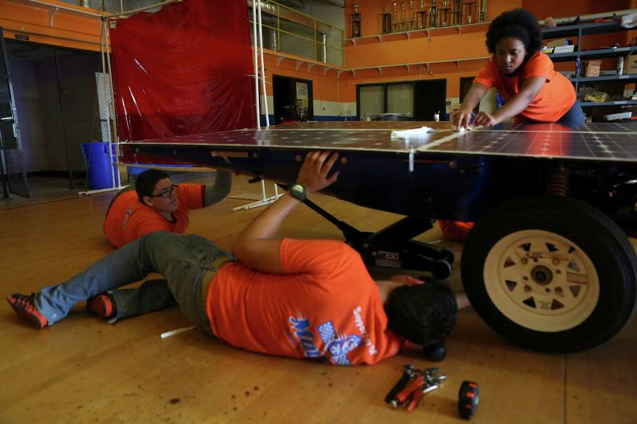 From left, Zach Funk, 16, David Castro, 18, and Mariah Morales, 15, prepare to make adjustments to the solar car Helios 2 after evaluating test drives on Friday, July 11, 2014, at James Madison High School in San Antonio. The three are members of the Madison Solar Car Initiative, a team of students that built Helios 2 and will take it to compete in this year's Solar Car Challenge, which begins July 18 in Fort Worth. Photo: Timothy Tai, San Antonio Express-News / © 2014 San Antonio Express-News
