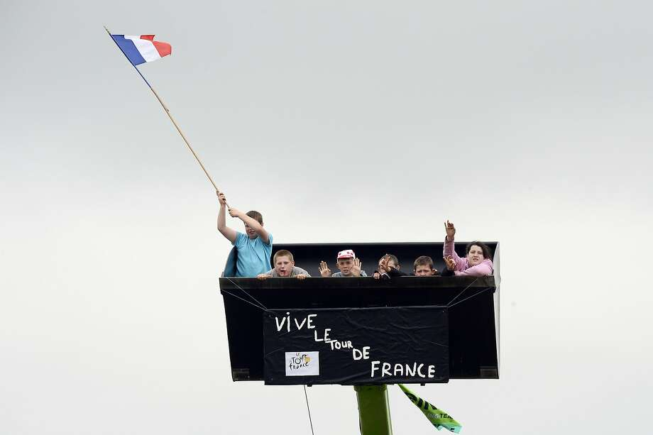 Choice seats: Children cheer on Tour de France cyclists from the bucket of a digger in a field along the seventh stage of the race between Epernay and Nancy, France. Photo: Lionel Bonaventure, AFP/Getty Images