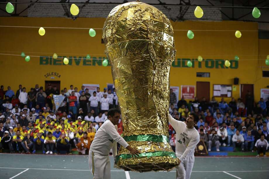 But will it fit in a cell? Inmates carry an oversized replica of the World Cup after a soccer tournament inside Lurigancho Prison in Lima. Four teams of six convicts, representing the countries that made it to the semifinals in Brazil, played for the title. Unlike in Brazil, however, the Netherlands won. Photo: Martin Mejia, Associated Press