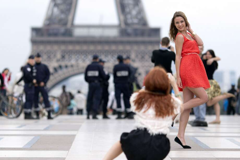 The little red dress: The Eiffel Tower makes the perfect backdrop for a photo shoot on Paris' Trocadero Esplanade. Photo: Kenzo Tribouillard, AFP/Getty Images