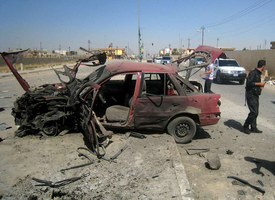 People inspect the site of a car bomb attack on cars lined up at a gas station in the oil rich city of Kirkuk, in northern Iraq, Thursday, July 10, 2014. The lightning sweep by the militants over much of northern and western Iraq the past month has dramatically hiked tensions between the country's Shiite majority and Sunni minority. At the same time, splits have grown between the Shiite-led government in Baghdad and the Kurdish autonomous region in the north.(AP Photo) Photo: Str, Associated Press
