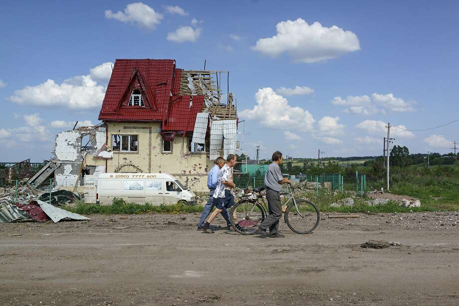 Locals walk past a destroyed house in the village of Semyonovka, near the eastern city of Slavyansk. The army has been fighting rebel forces for more than three months in the east. Photo: Alvaro Ybarra Zavala, Getty Images