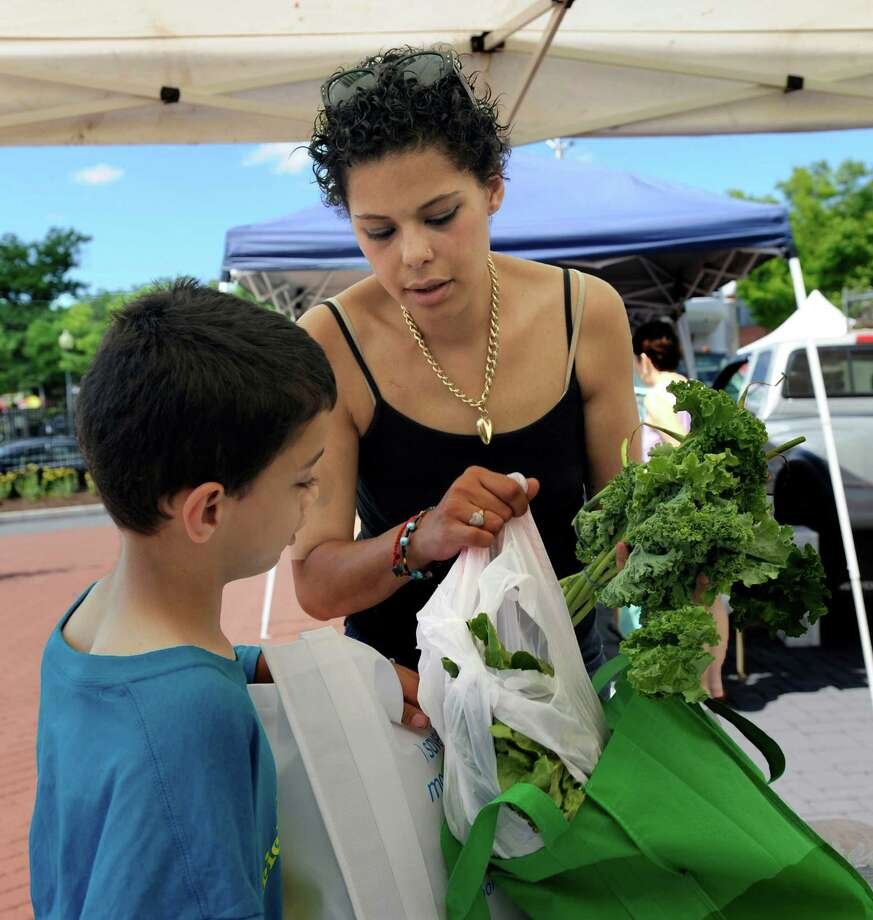 Elijah Perez, 9, and his mother is Giselle Torres, 33, look over some of the vegatables they purchased at the Danbury Farmers Market at Kennedy Park in Danbury, conn. Friday, July 11, 2014. Photo: Carol Kaliff / The News-Times