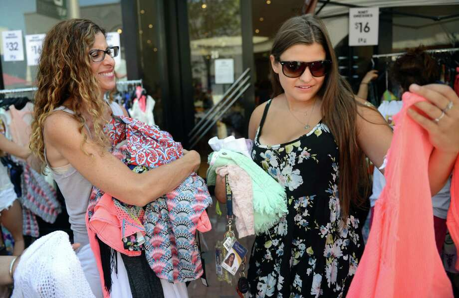 Wendie Vietze, of Trumbull, has her arms loaded with items from LF Westport for her daughter Jenna to try on Friday, July 11, 2014 during the annual Downtown Westport Sidewalk Sale. Photo: Autumn Driscoll / Connecticut Post