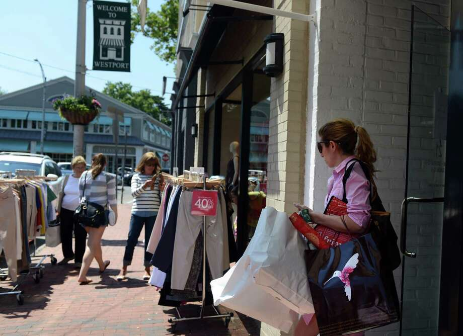 Shoppers hunt for bargains during the annual Downtown Westport Sidewalk Sale Friday, July 11, 2014.  The sale continues over the weekend. Photo: Autumn Driscoll / Connecticut Post