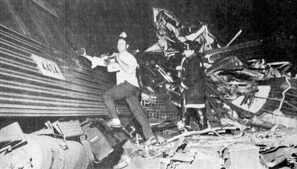 Rescue workers look for survivors following the collision of two Penn Central commuter trains near Hoyt Street in Darien on Aug. 20, 1969. Four people were killed and more than 40 were injured in the accident which prompted calls for increased safety.