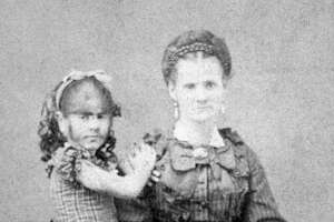 Circa 1875, Portrait of Annie Jones, the Bearded Girl (1865-1902), standing with her mother, 1870s. She was billed by P T Barnum as 'the infant Esau'.