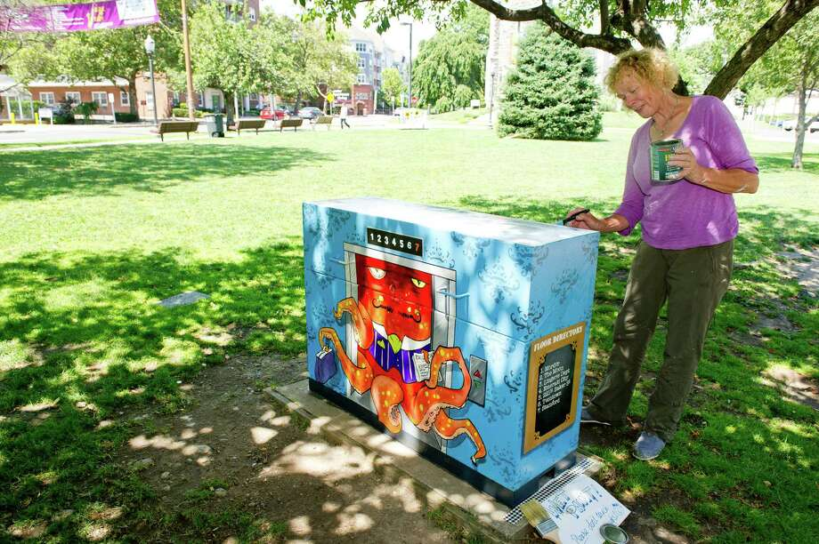 Sheila Cartwright puts varnish on a signal box painted by her son, Mark Greenbaum of New Milford, Conn., at Latham Park as part of a Downtown Special Services District program on Friday, July 11, 2014. Photo: Lindsay Perry / Stamford Advocate